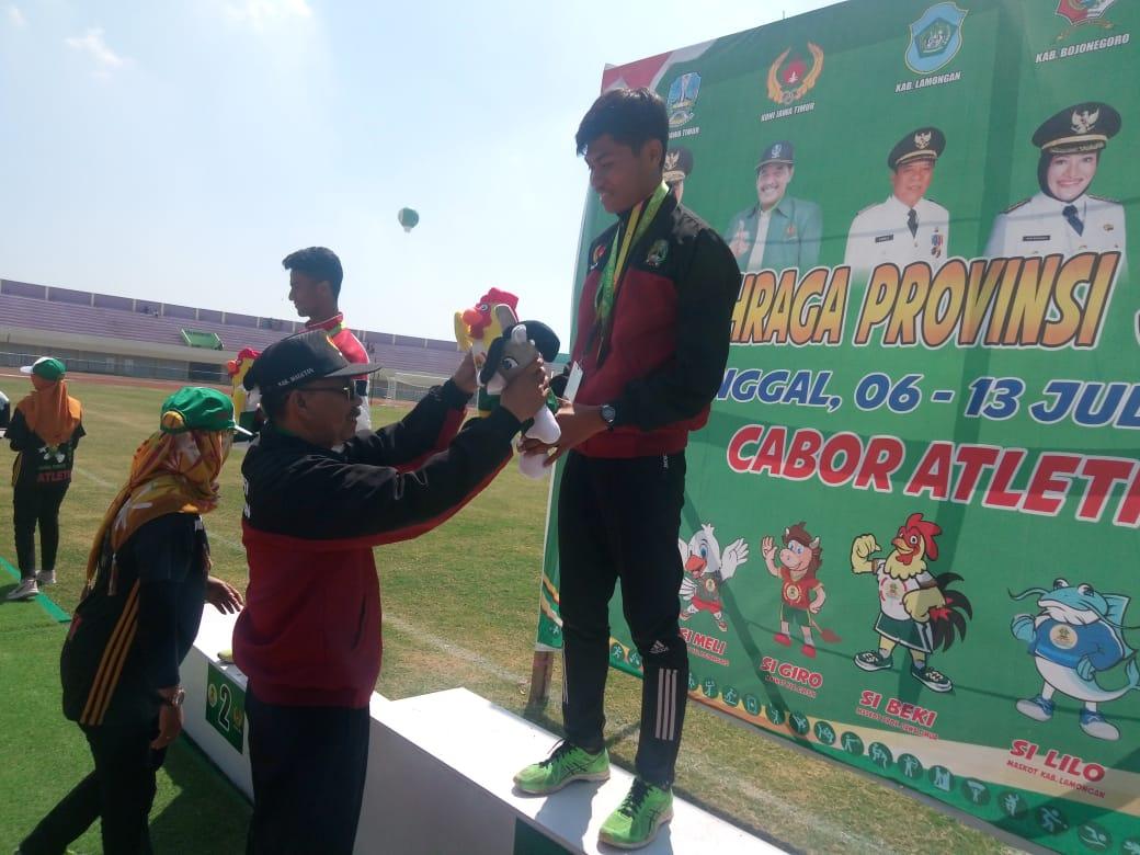 Ketua KONI Magetan, Sofyan, Mengalungkan Medali Kepada Angga Septiyan Prastyo, Peraih Medali Emas Cabor Jalan Cepat 10.000 Meter. ( Ist For Magetan Today)