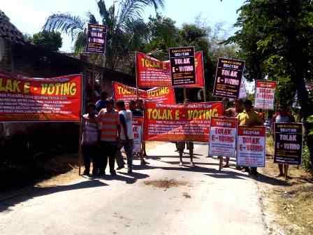 Warga Belotan Bawa Banner Menolak Pilkades e-Voting. ( Norik/Magetan Today)