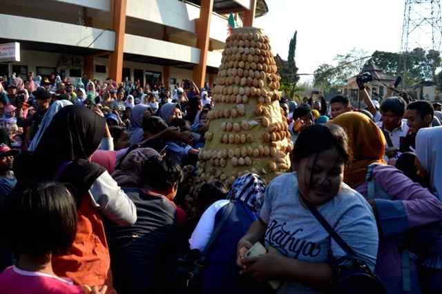 Warga Berebut Kue Bolu  Yang Dibentuk Gunungan di Halaman GOR Ki Mageti, Magetan. ( Norik/Magetan Today)