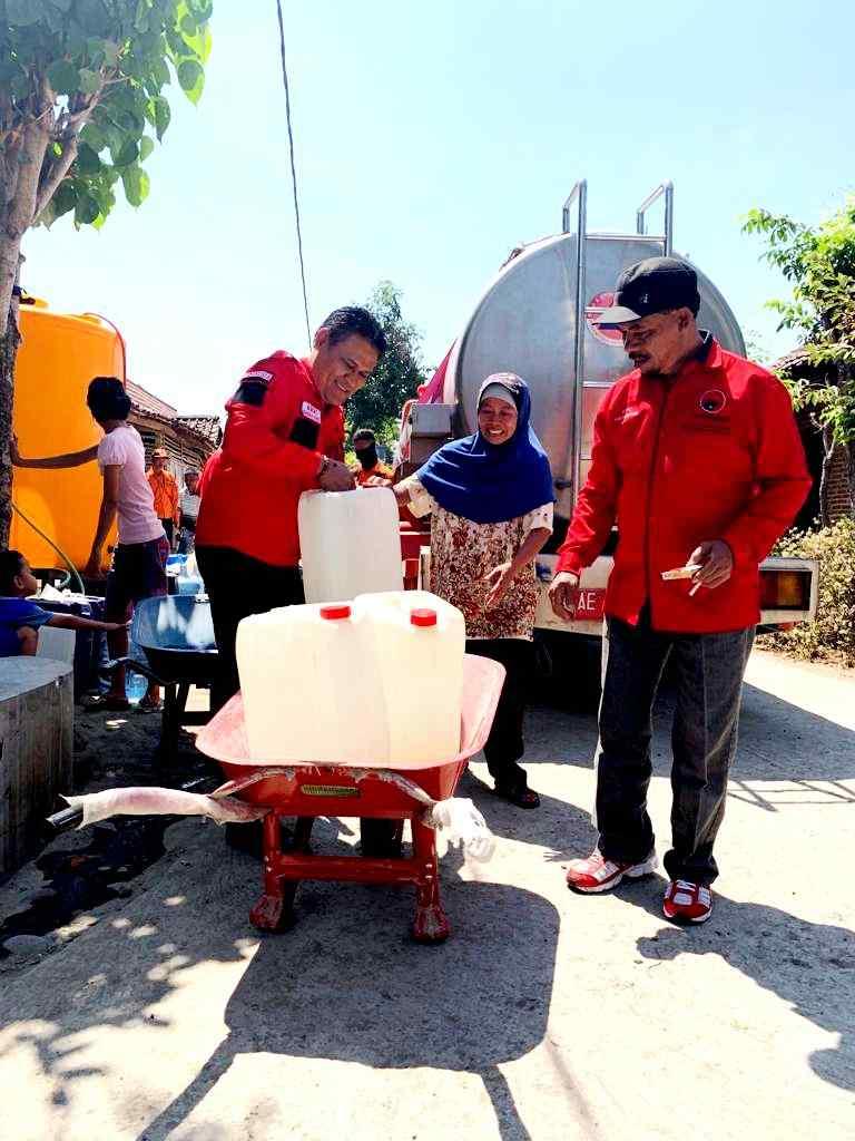 Ketua DPC PDIP Magetan, Sujatno bersama Ketua Fraksi PDI Perjuangan, Suyatno membantu  warga membawa air bersih. ( Norik/Magetan Today).