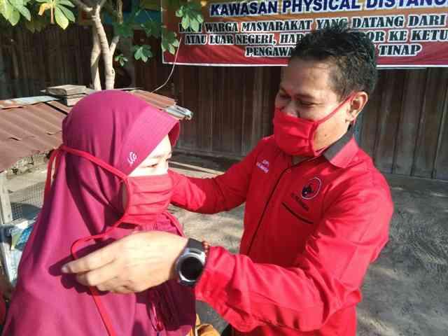 Sujatno, Ketua DPC PDIP Magetan Memakaikan Masker Kepada Warga. ( Norik/Magetan Today)