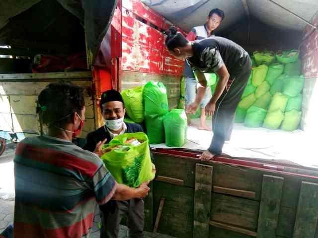 Nur Wachid, Ketua DPC PKB Magetan, Membantu Menurunkan Paket Sembako. ( Norik/Magetan Today).