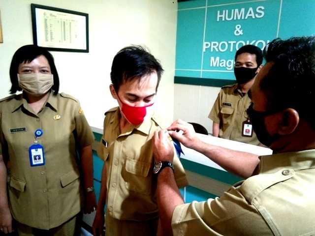 Kabag Humas dan Protokol, Suwito Menyematkan Pita Kepada Satgas Disiplin Protokol Kesehatan. (Norik/Magetan Today).