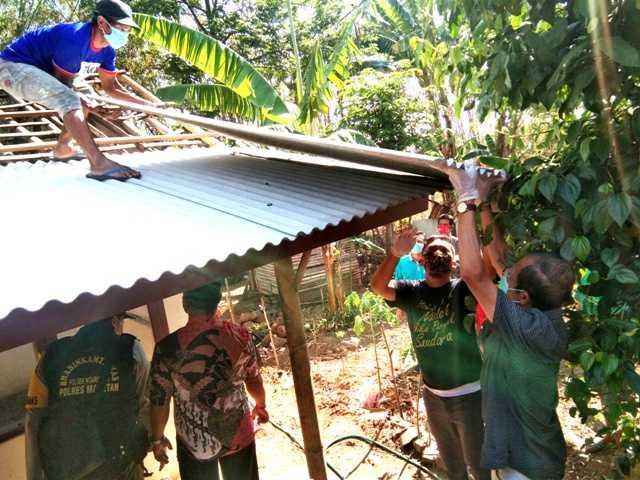 Bupati Magetan Suprawoto membantu mengangkat material RTLH yang akan diperbaiki. (Norik/Magetan Today).