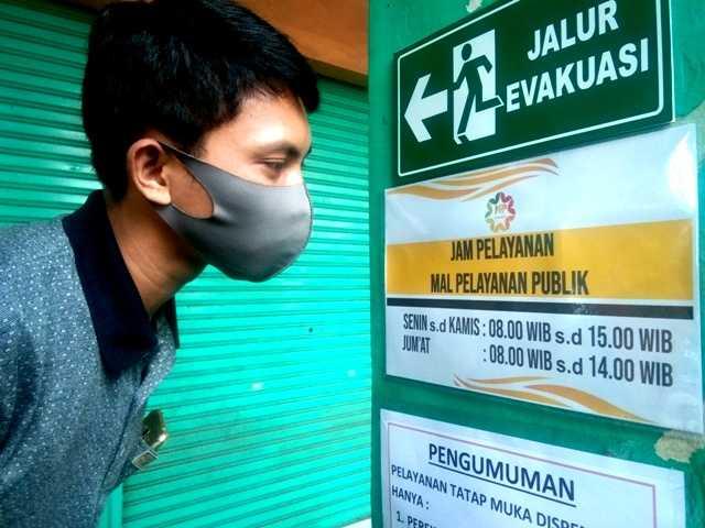 Warga Melihat Jam Operasional MPP Magetan. ( Norik/Magetan Today)
