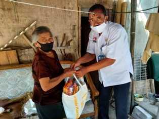 Pegawai Kecamatan Sidorejo Menyerahkan Bantuan Sembako Untuk Mbah Sadinah. ( Norik/MagetanToday)